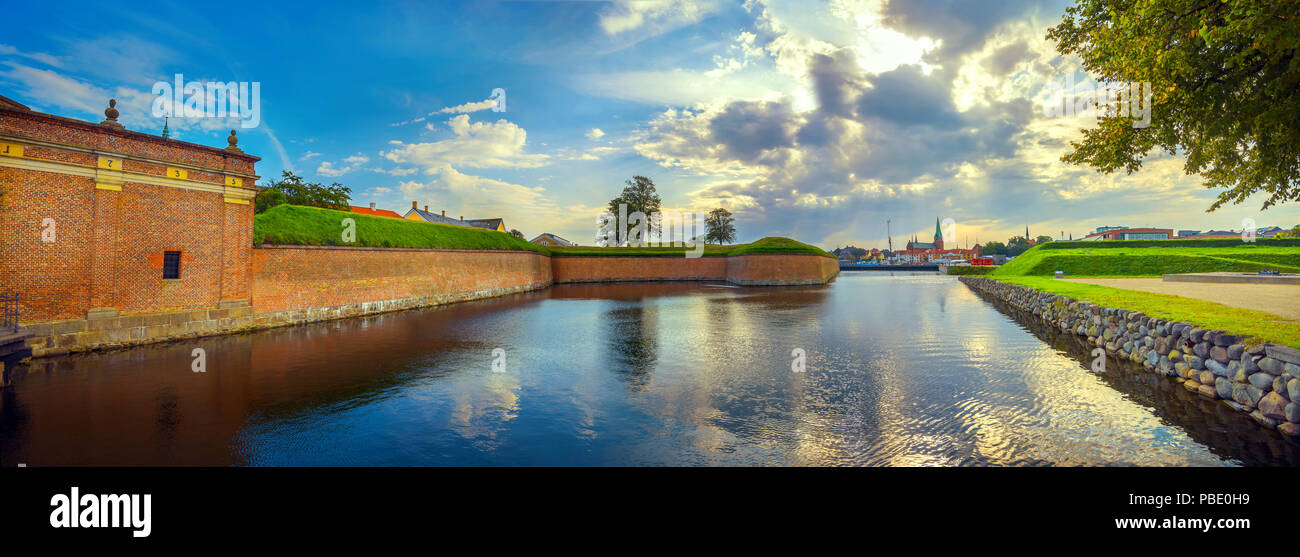 Panoramic landscape with fortress walls, water moat of Kronborg castle and town at sunset. Helsingor, Denmark - Stock Image