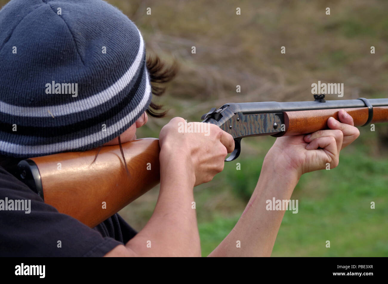 Young man shooting an H&R .44 Magnum rifle at a Corpus Christi, Texas gun range. - Stock Image
