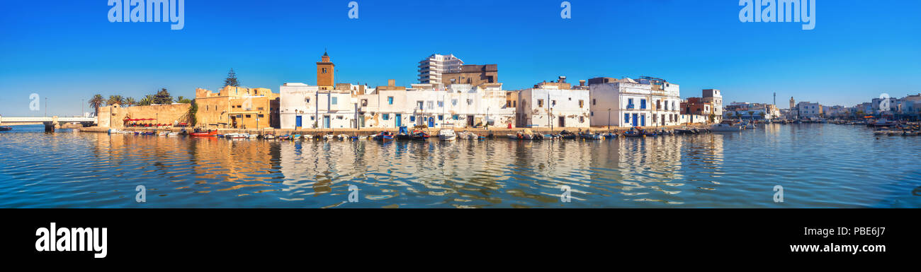 Panoramic view of waterfront with kasbah wall and picturesque houses in old port at sunset. Bizerte, Tunisia, North Africa - Stock Image