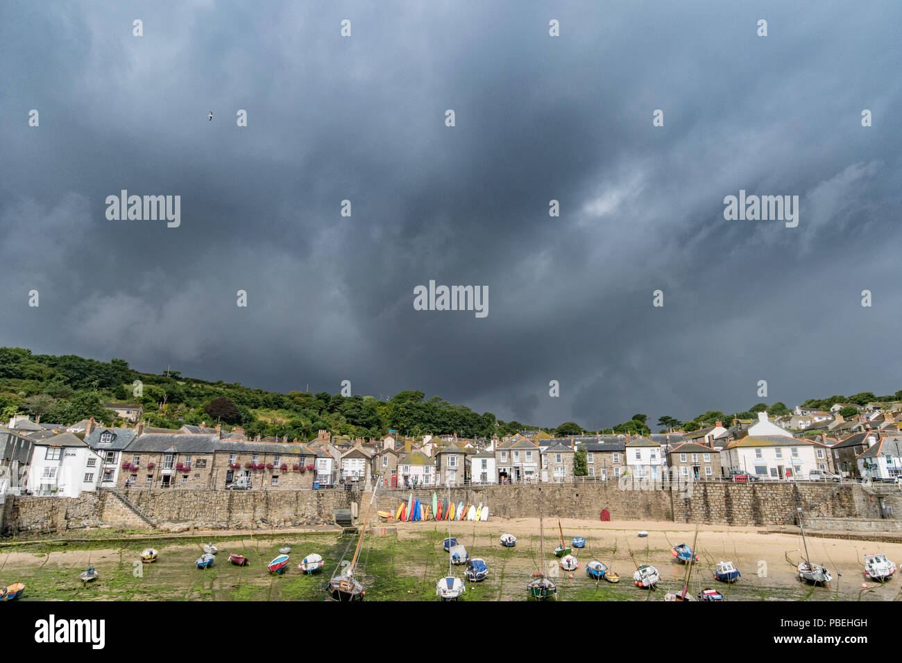 Mousehole, Cornwall, UK. 28th July 2018. UK Weather. Black skies and heavy downpours across the far south west of Cornwall today, as the heatwave breaks. Credit: Simon Maycock/Alamy Live News - Stock Image