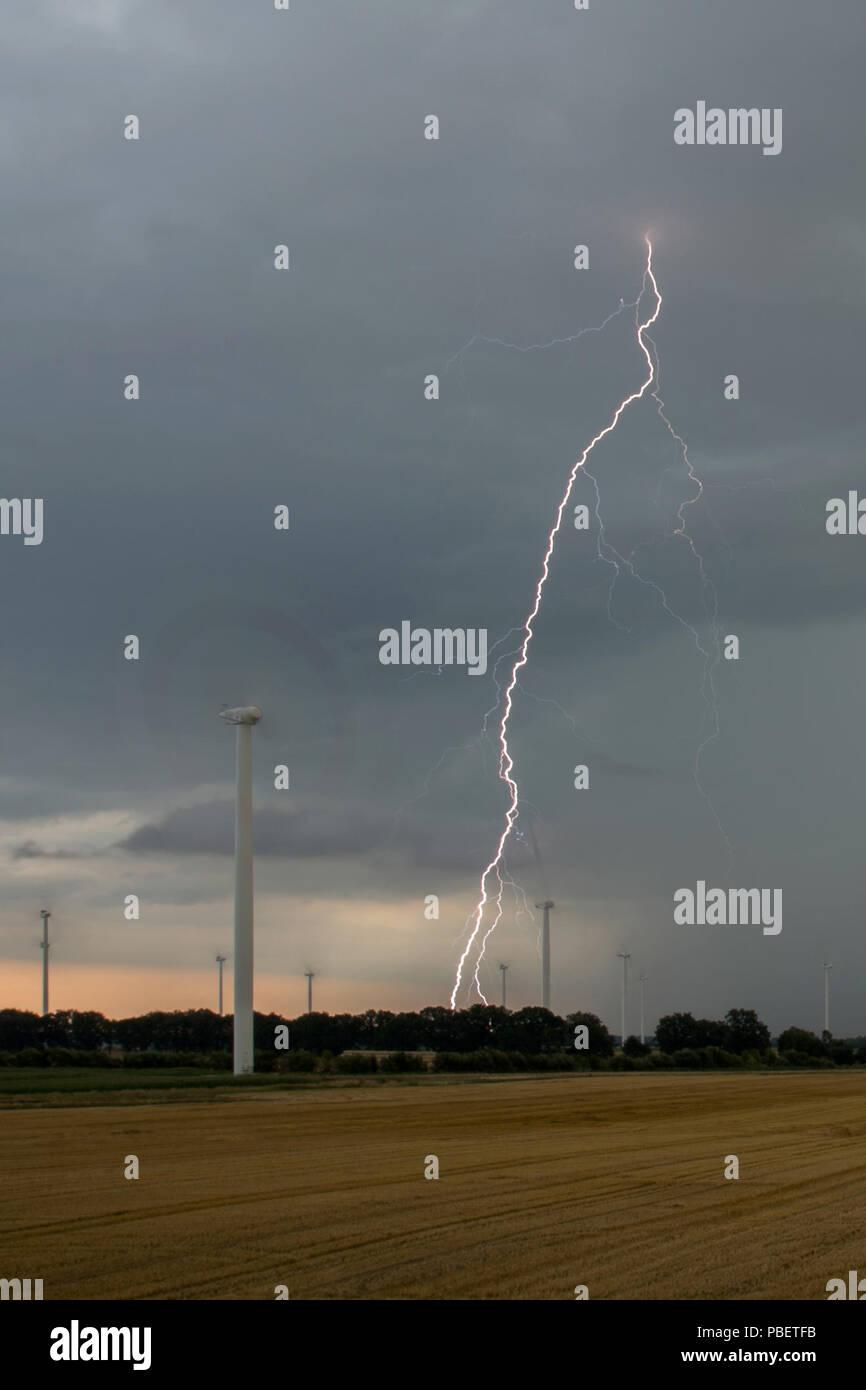 Neuruppin, Germany. 28th July, 2018. A lightning strikes over a field near Neuruppin. Credit: Arne Immanuel Bänsch/dpa/Alamy Live News - Stock Image