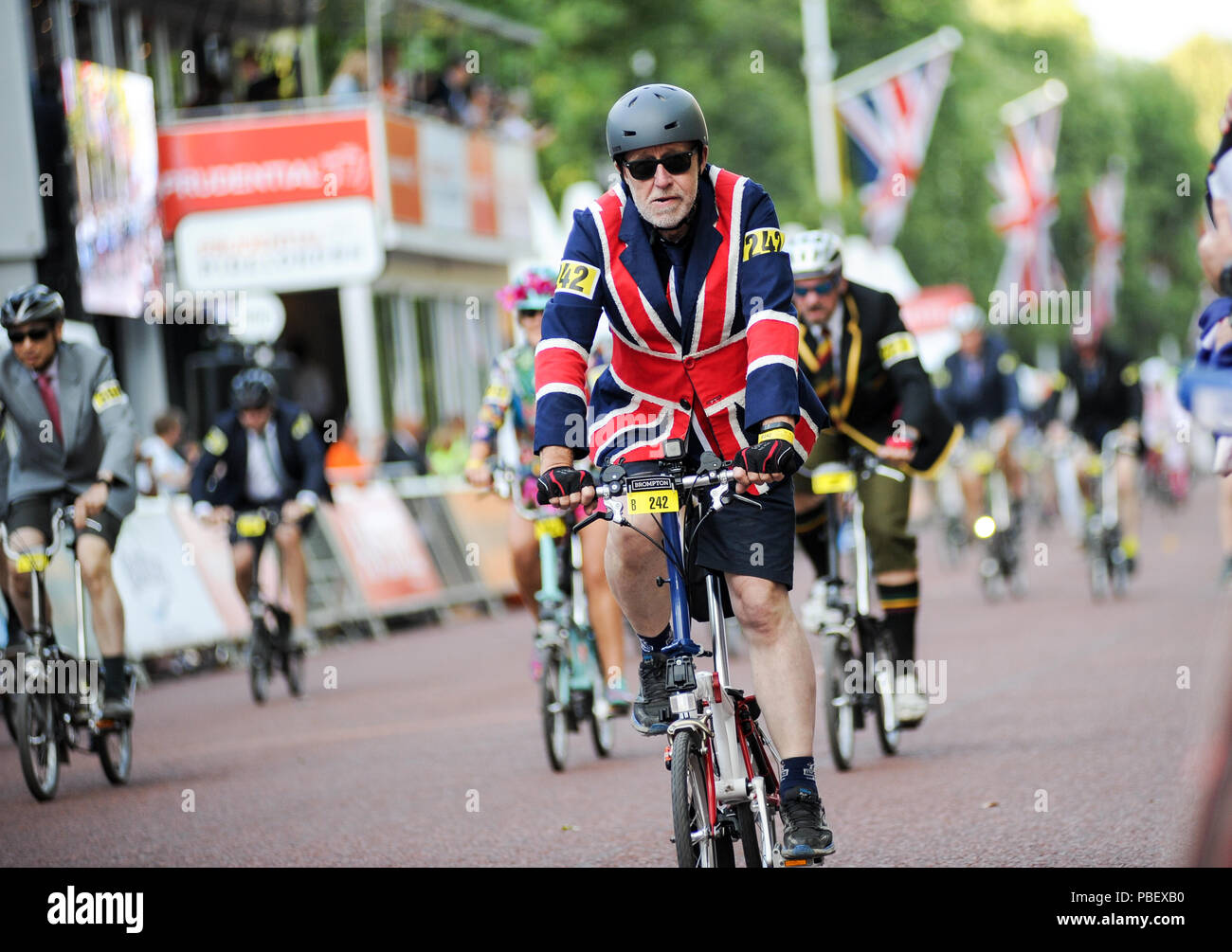 Central London, UK, 28th July 2018. Riders race down The Mall during the Brompton World Championship Final, part of the Prudential RideLondon Festival of Cycling weekend. This unique and hugely enjoyable event takes the form of a Le Mans style start as 500+ smartly-dressed competitors make a mad dash to unfold their bikes before setting off on the famous eight lap circuit around St James' Park. @ David Partridge / Alamy Live News Stock Photo