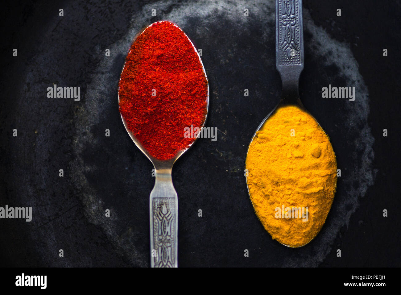 Two spoonfuls of Indian spices. These are key ingredients of Indian food across the entire subcontinent. These are called Turmeric and red Chilly. - Stock Image