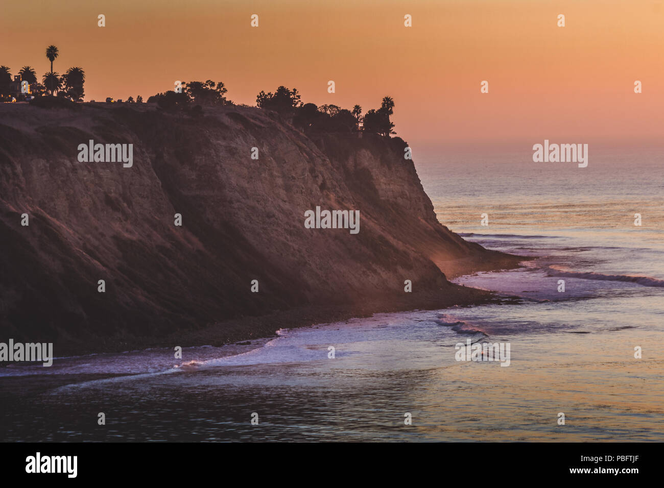 Long-exposure shot taken after sunset of coastal Palos Verdes Estates with silhouette of steep cliffs, trees, and homes as well as smooth ocean waves, - Stock Image
