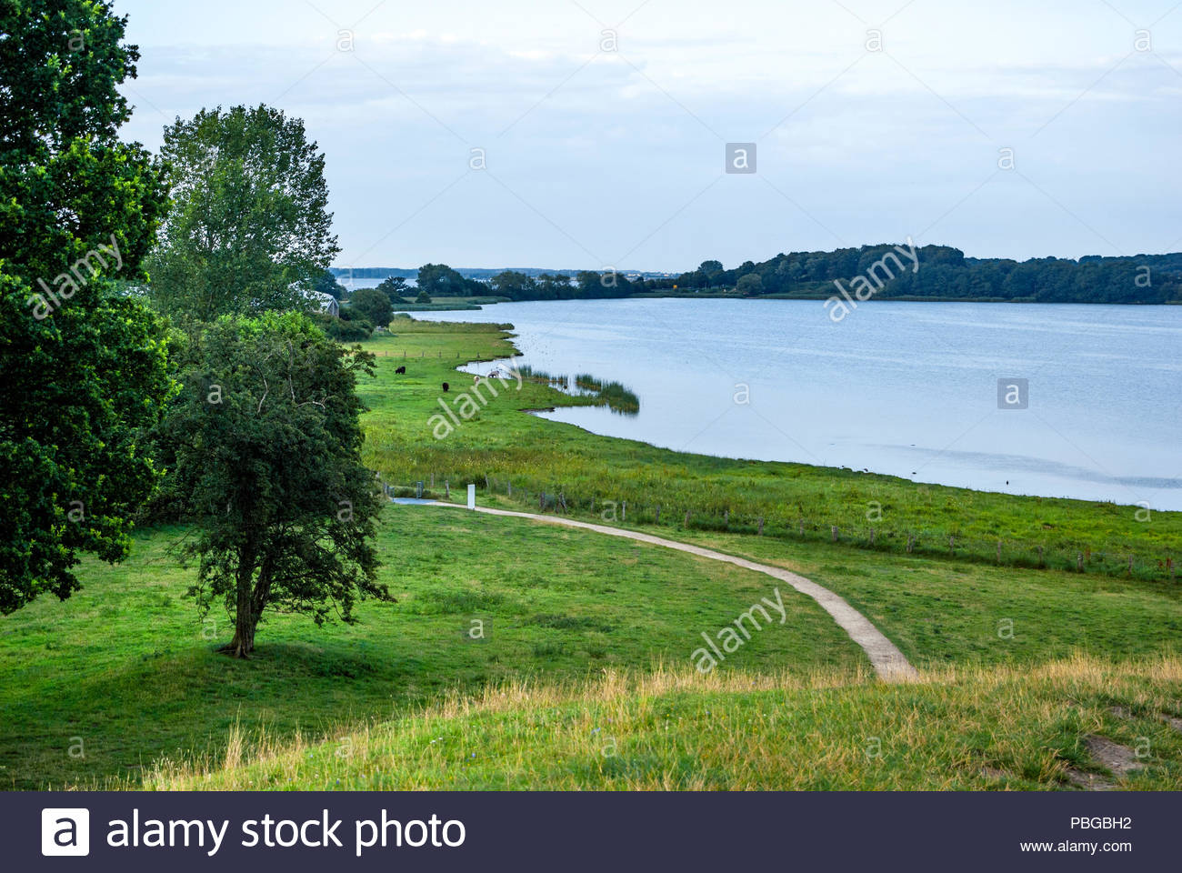 Haddebyer Noor and the Schlei beyond are seen from atop the Dannevirke rampart that encircles Haithabu. - Stock Image