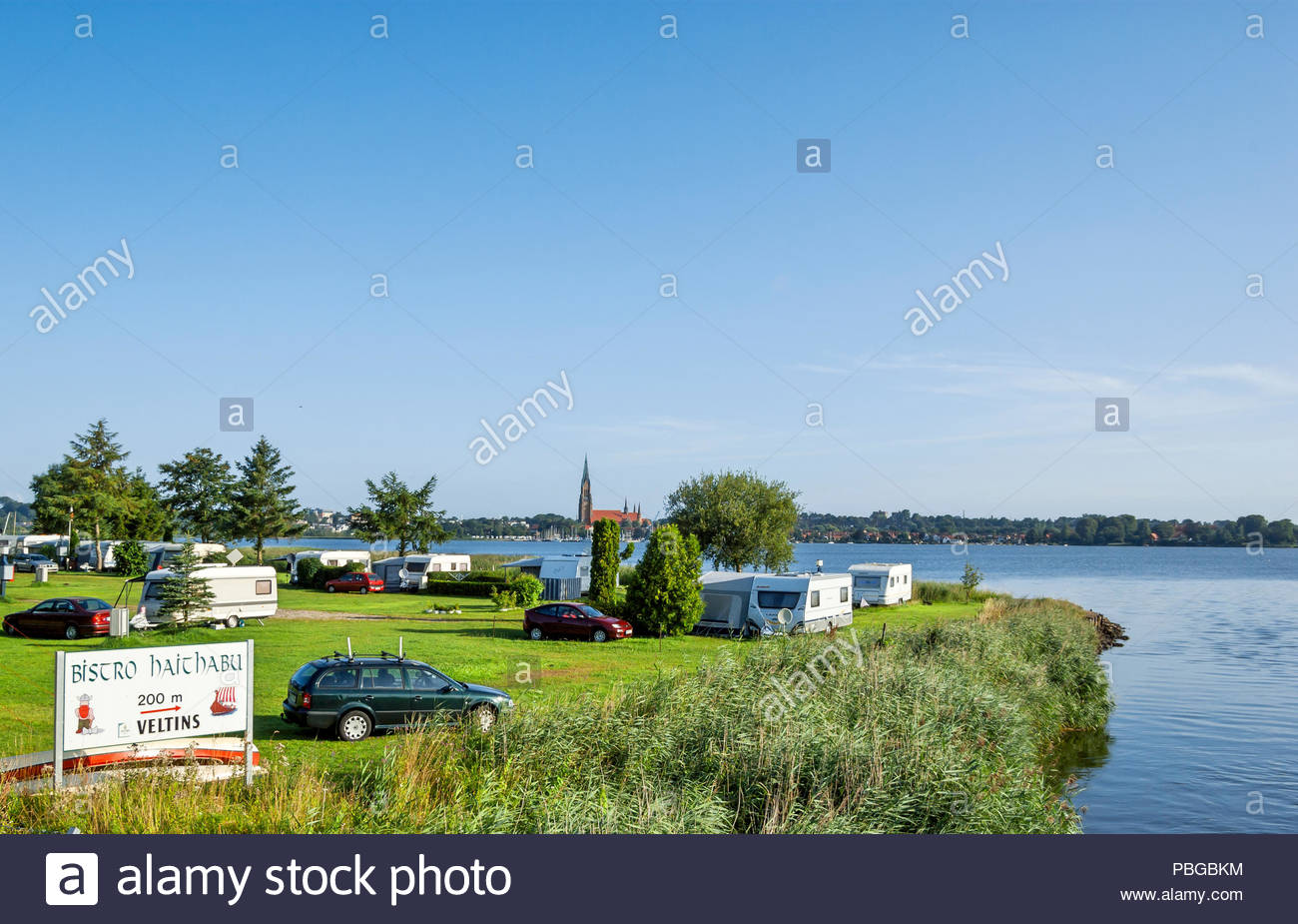 The Haithabu campground, city of Schleswig in background, is across the road from the Wikinger Museum, Haithabu, by the inlet to the Haddebyer Noor. - Stock Image