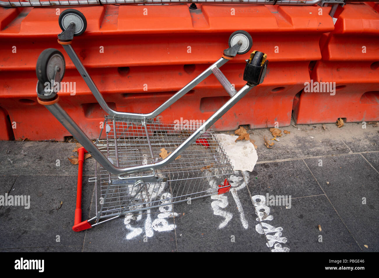 a shopping trolley is left upside down on foot path in city near construction site. - Stock Image