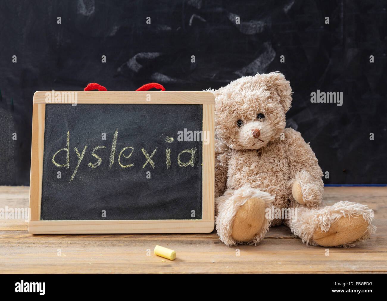 Dyslexia and school. Teddy bear and a blackboard. Dyslexia text drawing on the blackboard - Stock Image