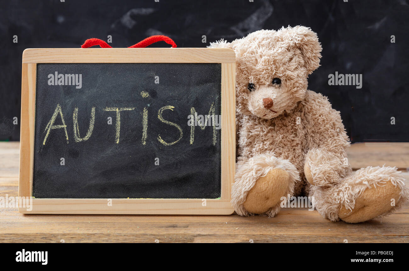 Autism and school. Teddy bear and a blackboard. Autism text drawing on the blackboard - Stock Image