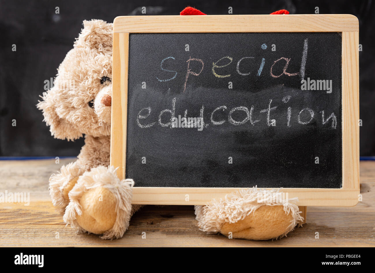 Special education. Teddy bear hiding behind a blackboard. Special education text drawing on the blackboard - Stock Image