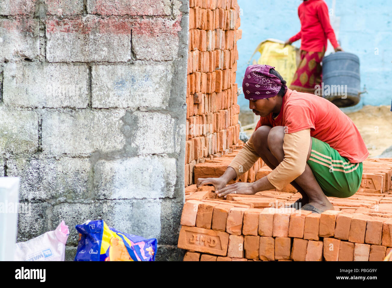 Worker piling up bricks in Pokhara, Nepal - Stock Image