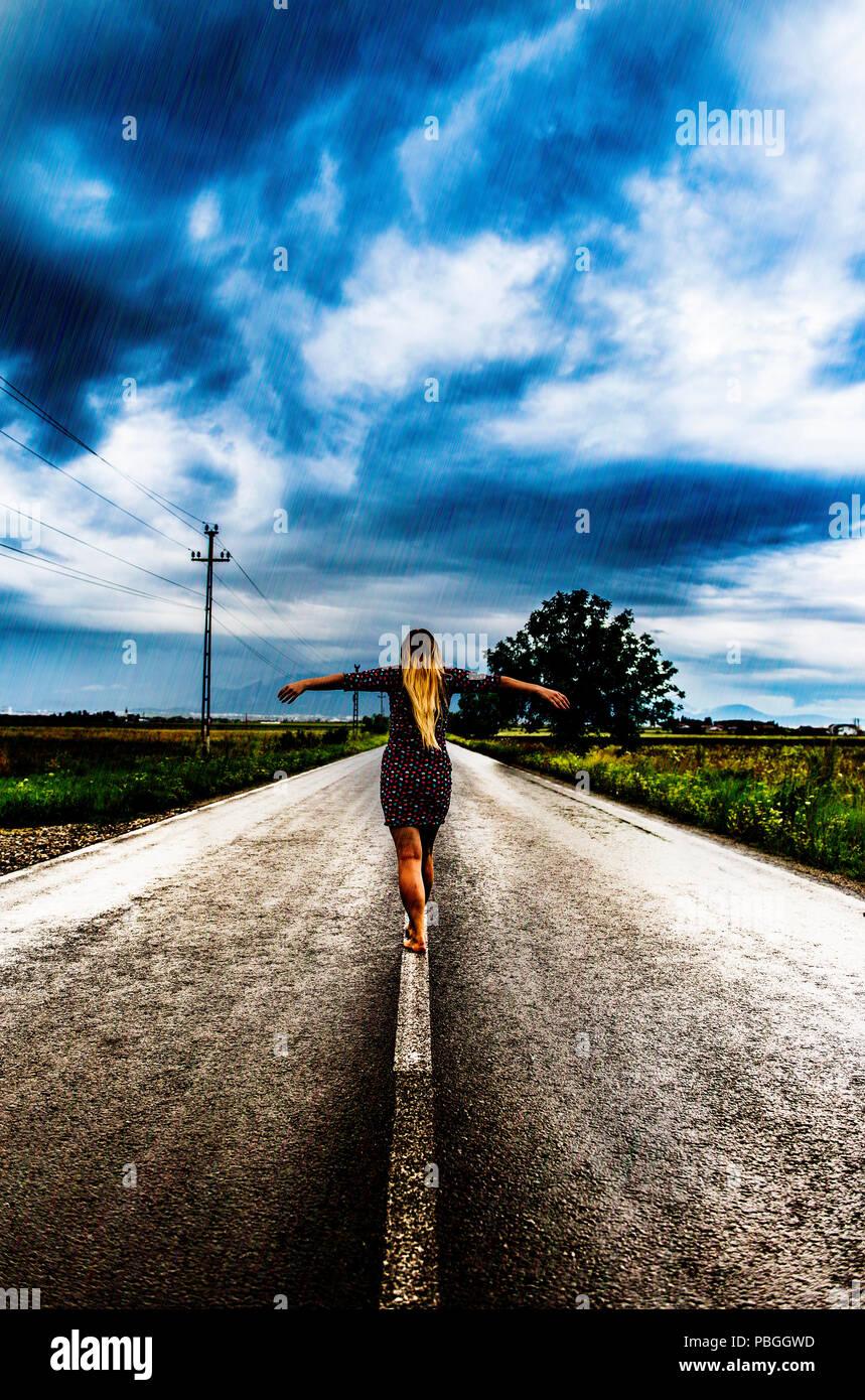 GIrl on the road walking barefoot - Stock Image