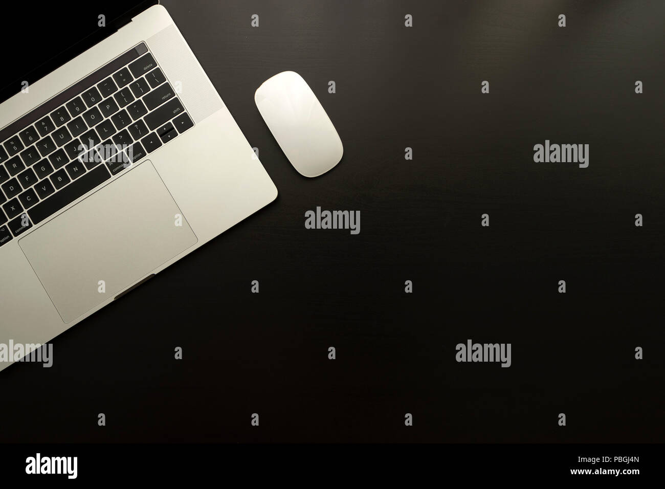 laptop and mouse over black wooden table monochromatic flat lay composition - Stock Image