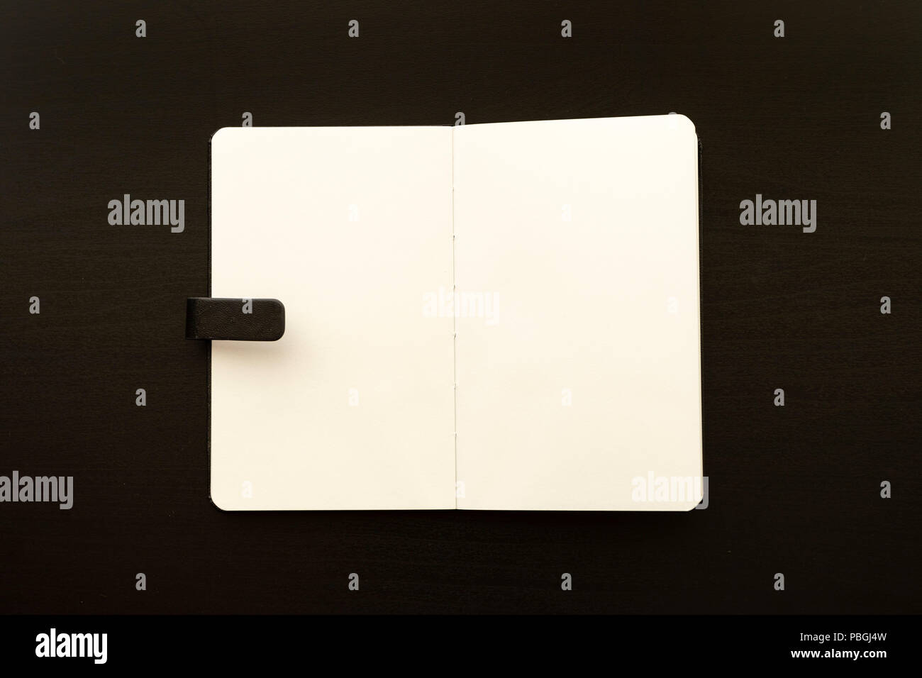 sketchbook over black wooden table monochromatic flat lay composition - Stock Image