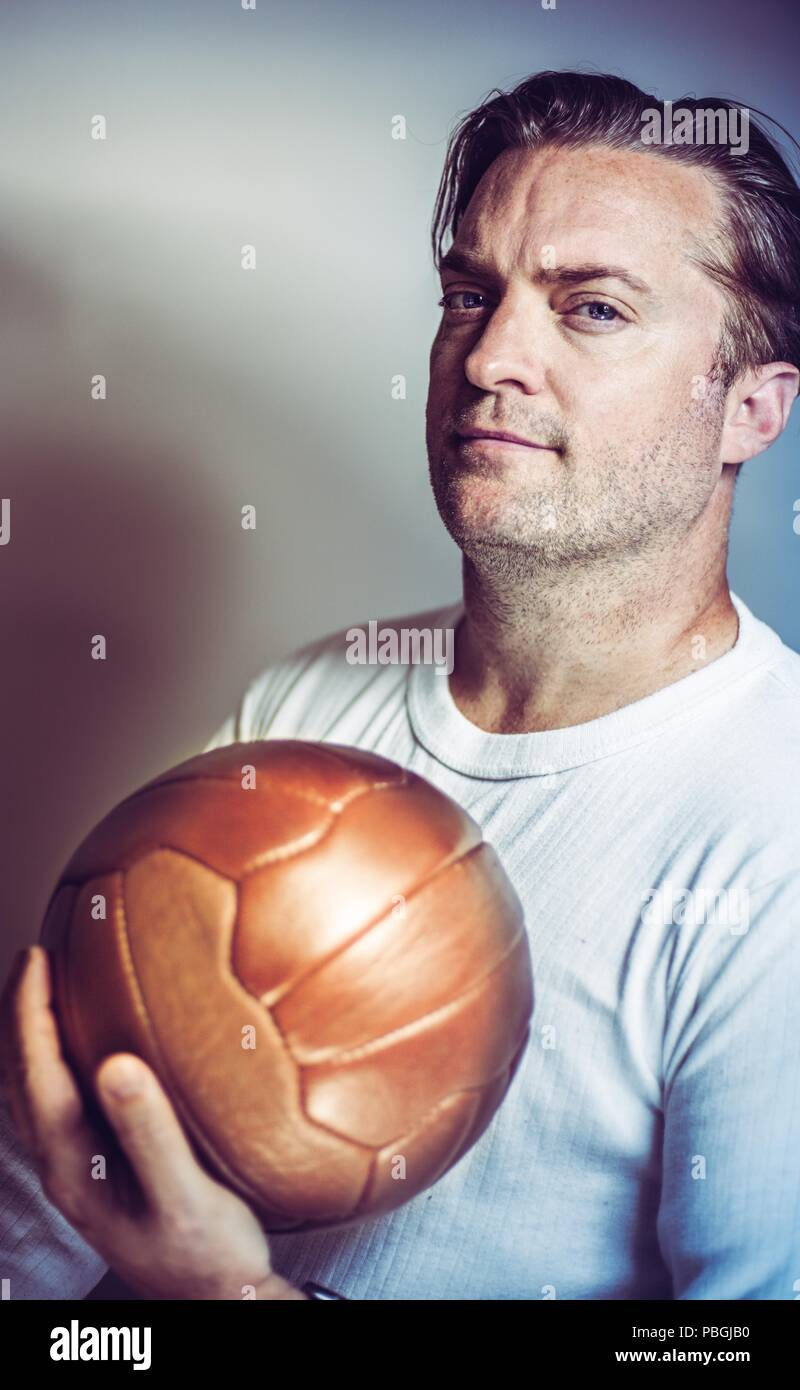 portrait of a soccer coach holding a vintage ball Stock Photo