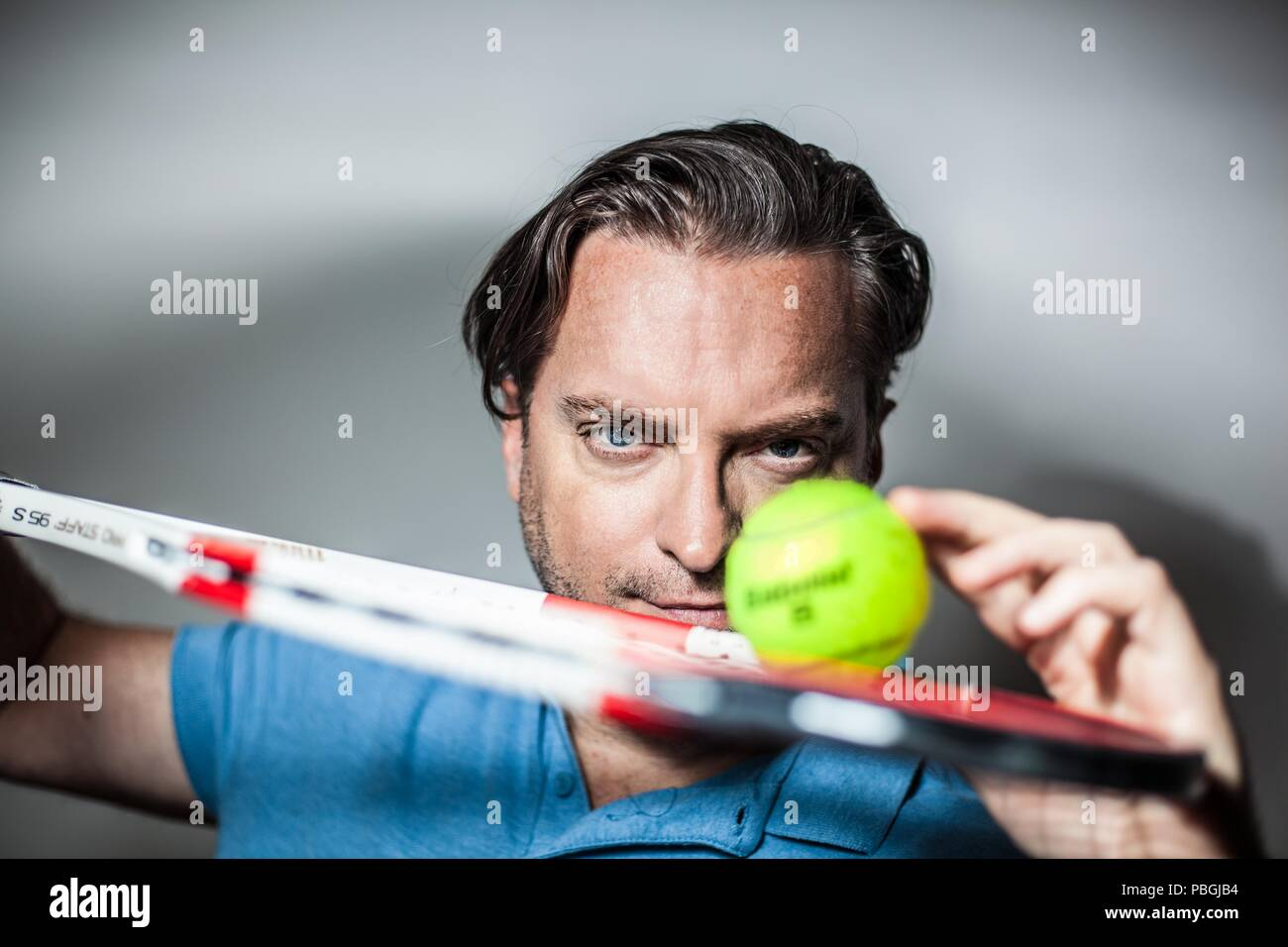 portrait of a handsome man with a tennis racket Stock Photo