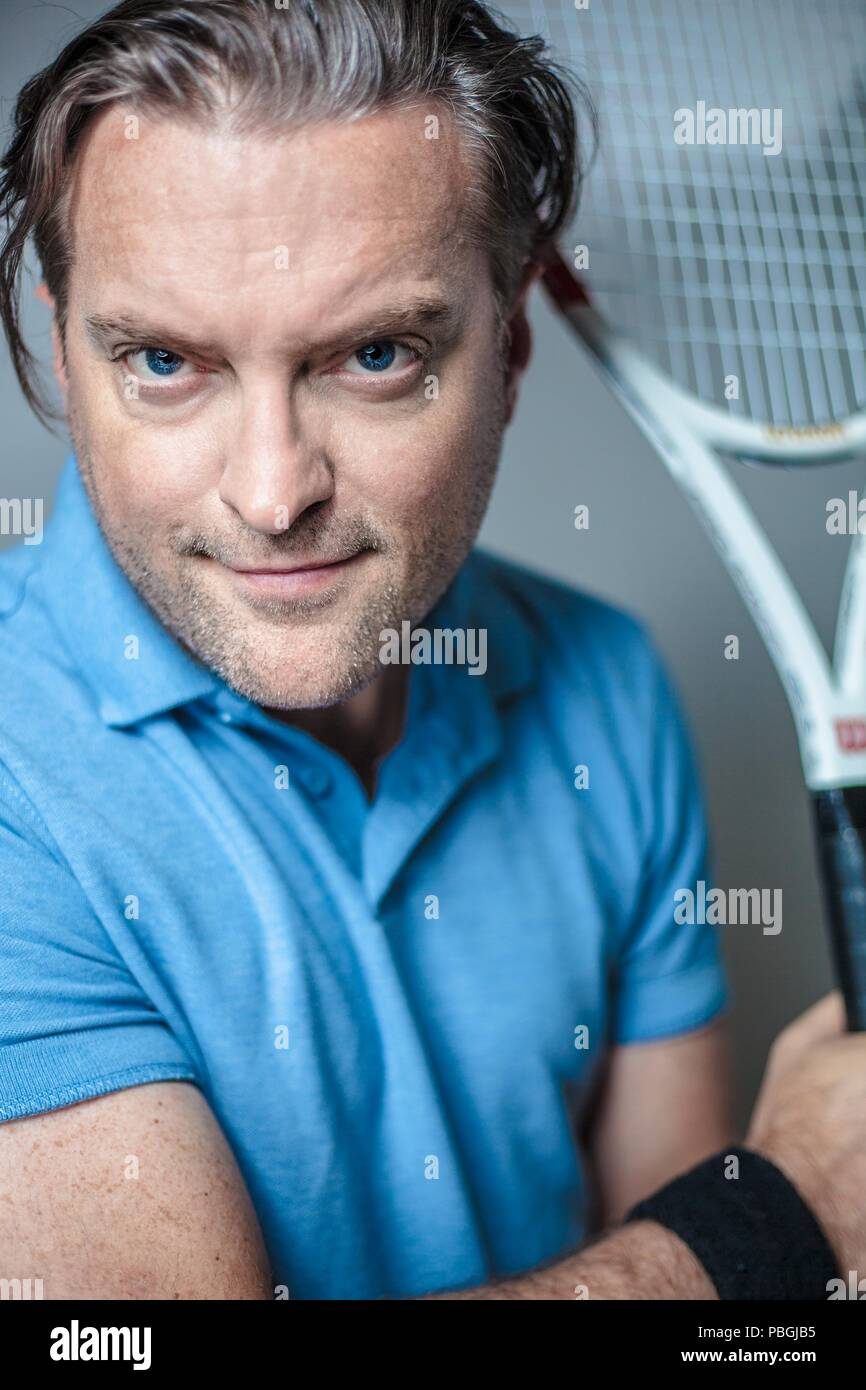 portrait of a handsome man with a tennis racket - Stock Image