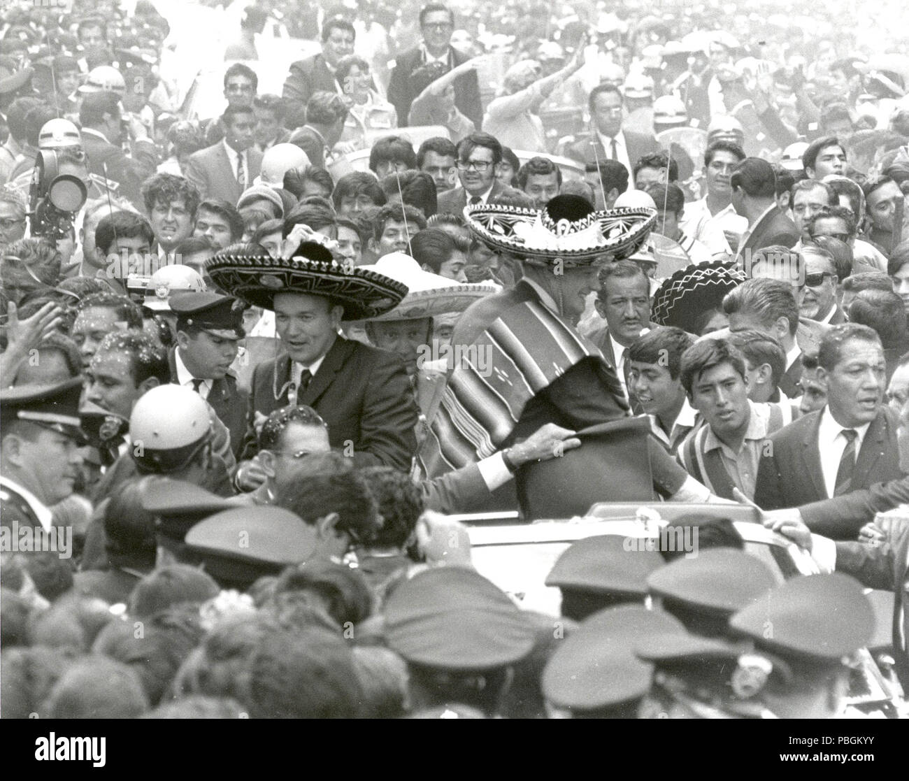 The Apollo 11 astronauts, Neil A. Armstrong, Edwin E. Aldrin, Jr., and Michael Collins, wearing sombreros and ponchos, are swarmed by thousands in Mexico City as their motorcade is slowed by the enthusiastic crowd. - Stock Image