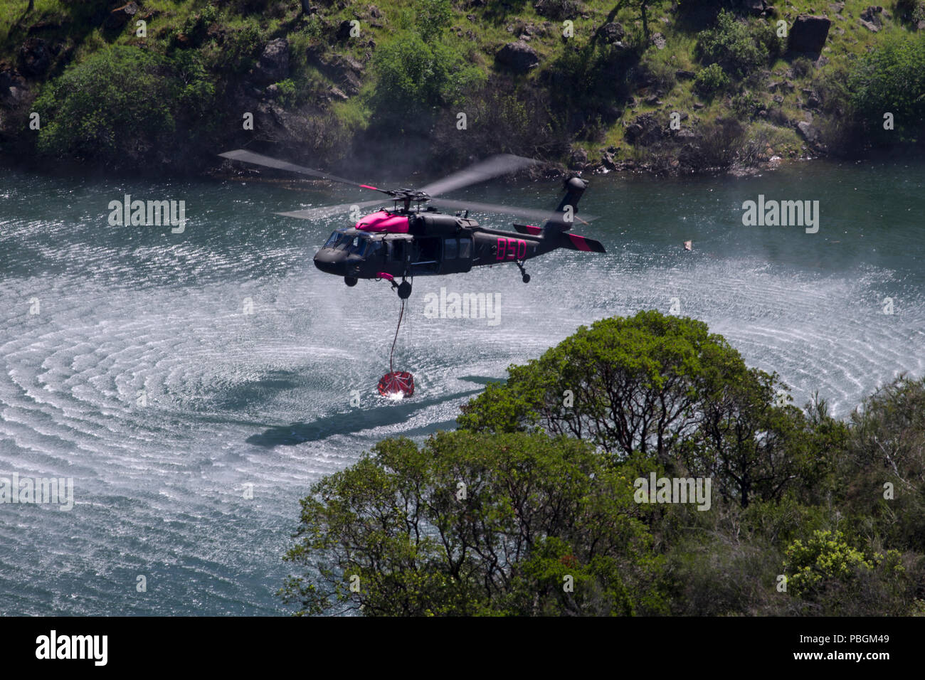 An Army National Guard UH-60 Black Hawk helicopter picks up water from Pardee Reservoir, in Ione, California, Saturday, April 14, 2018, during interagency aircrew training with CAL FIRE. Cal Guard helicopter crews and support personnel gathered for three days of joint wildfire aviation training to prepare for heightened fire activity in the summer and fall. (U.S. Air National Guard photo by Senior Airman Crystal Housman) Stock Photo
