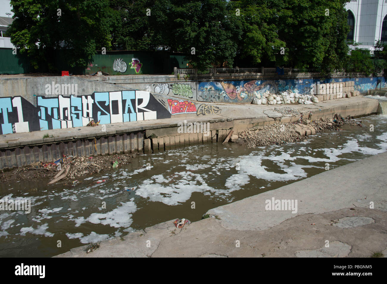 Garbage, pollution and graffiti along the Gombak River in downtown Kuala Lumpur - Stock Image