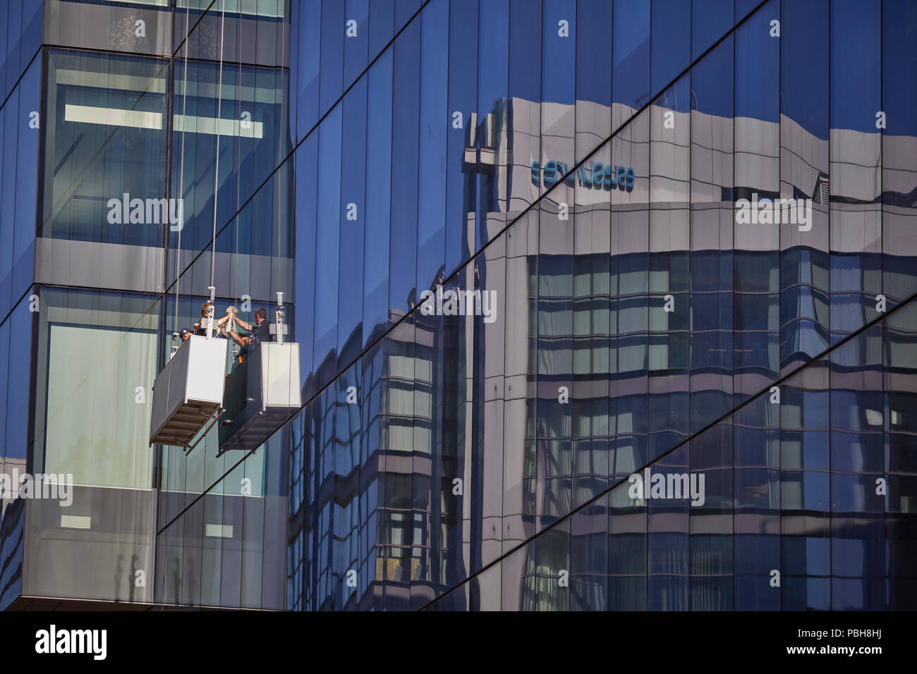 Windowcleaners in a bucket Manchester city centre No.1 Spinningfields Allied London in Hardman Square financial district landmark hi rise office build - Stock Image
