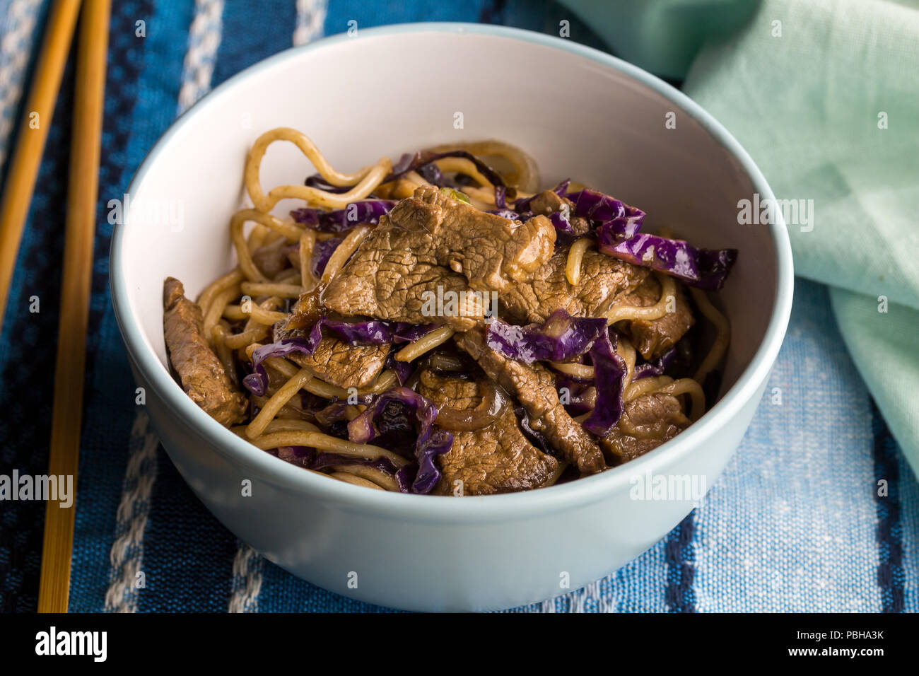 Steak, noodles and purple cabbage closeup in bowl with chopsticks - Noodle meal - Stock Image