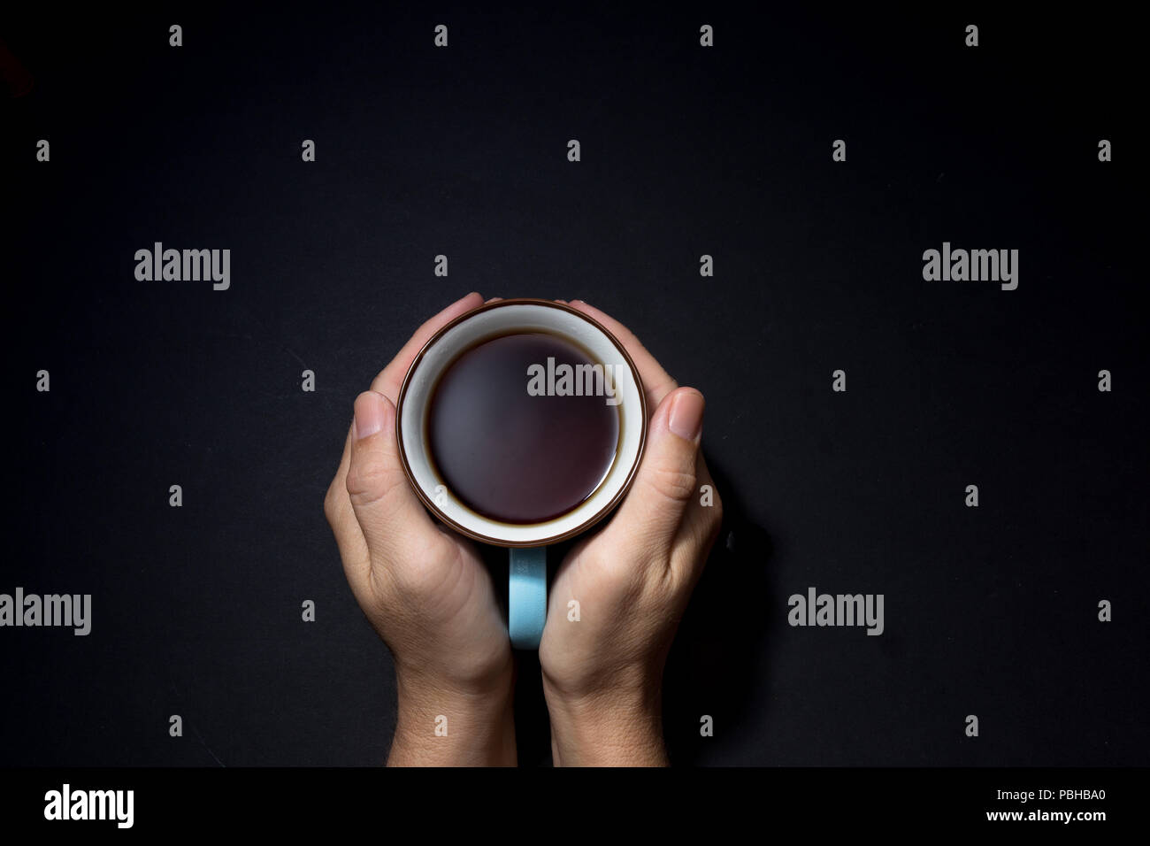 cup in palm on the black background - Stock Image
