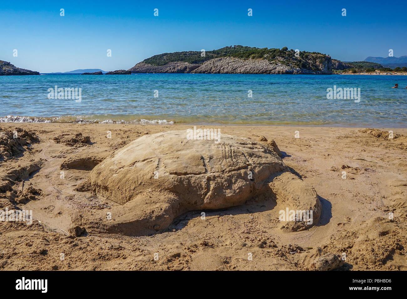 Amazing sea turtle on the beach hand made of sand in Voidokilia, Messenia, Greece - Stock Image