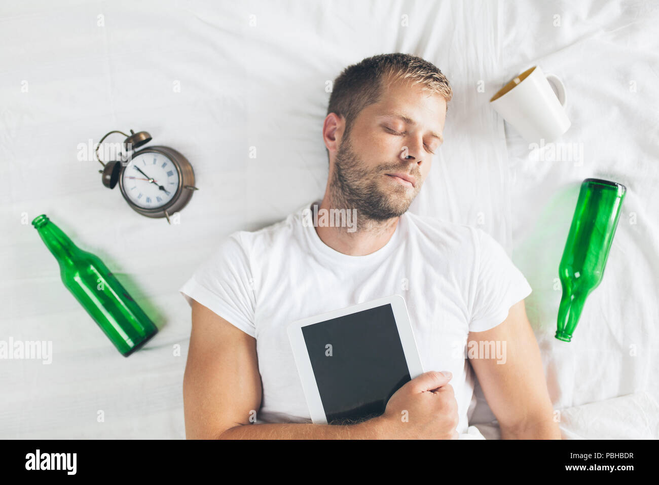 Young handsome man in bed the morning after night out drinking - Stock Image