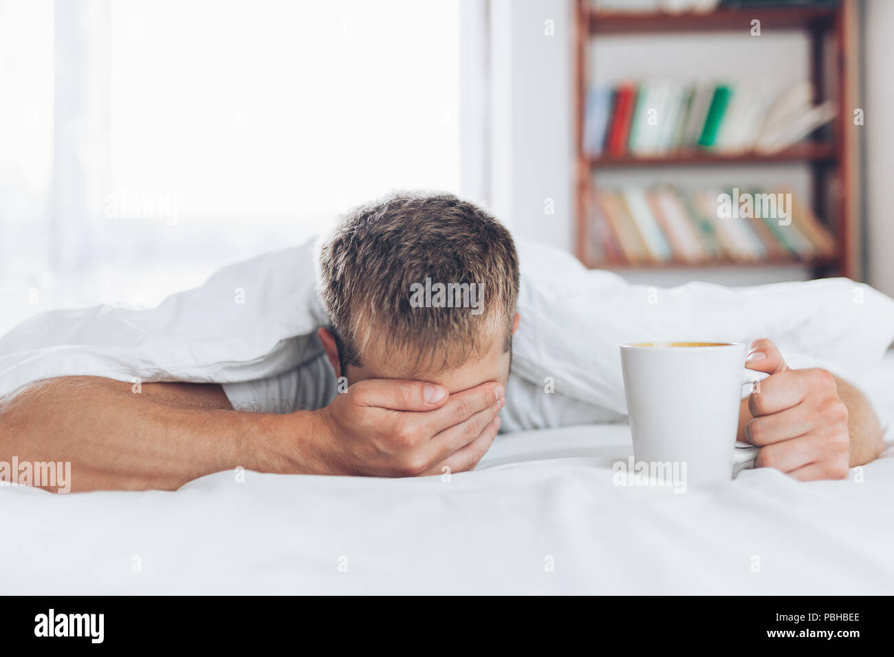 Man trying to wake up in the morning after night out - Stock Image