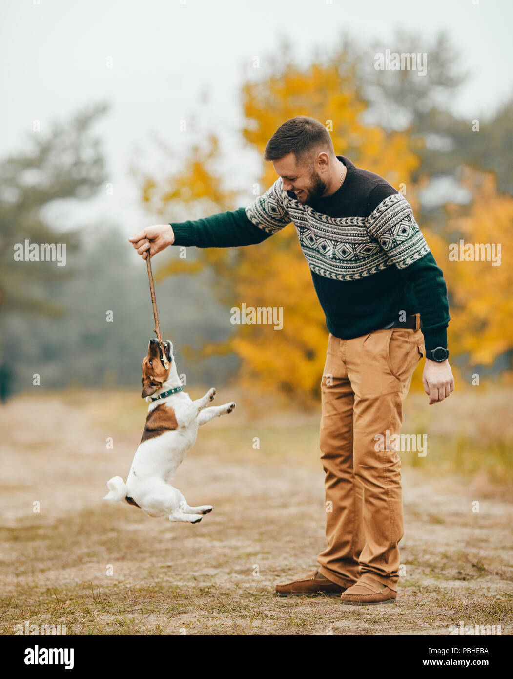 Young man has fun and plays with his dog during walk in autumn forest. - Stock Image