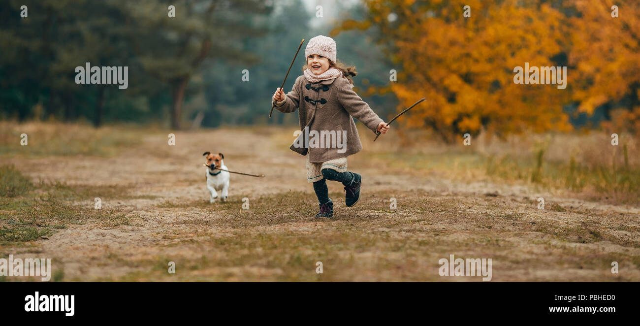 Child girl runs, has fun and plays with his dog during walk in autumn forest. - Stock Image