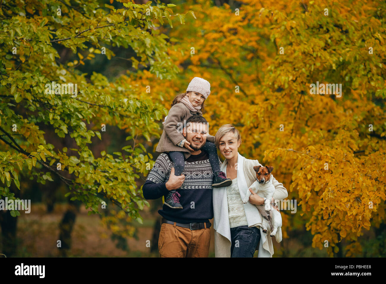 Parents with their daughter walk with dog in autumn forest. - Stock Image