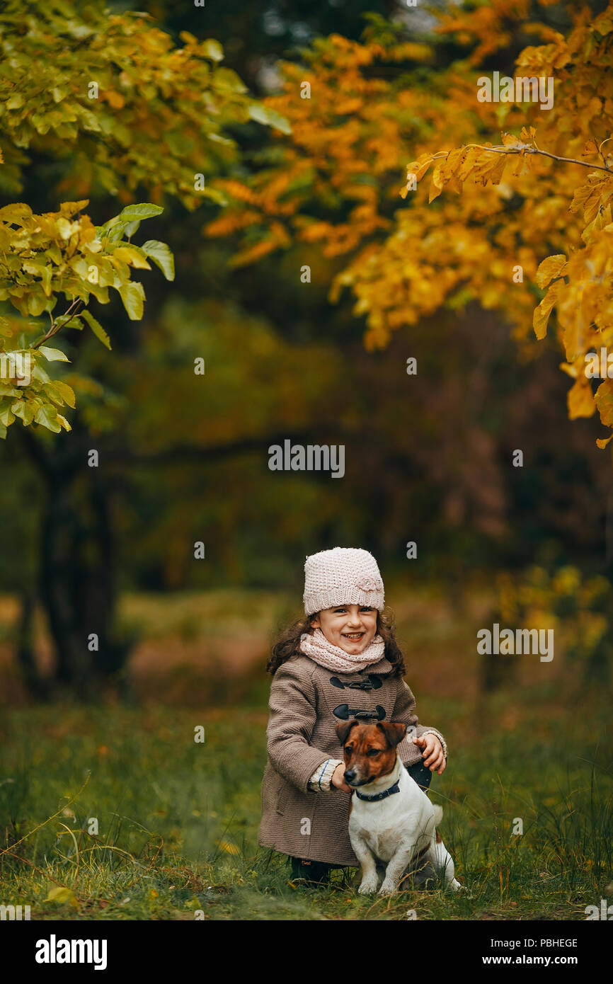 Child girl sits and plays with his dog during walk in autumn forest. - Stock Image