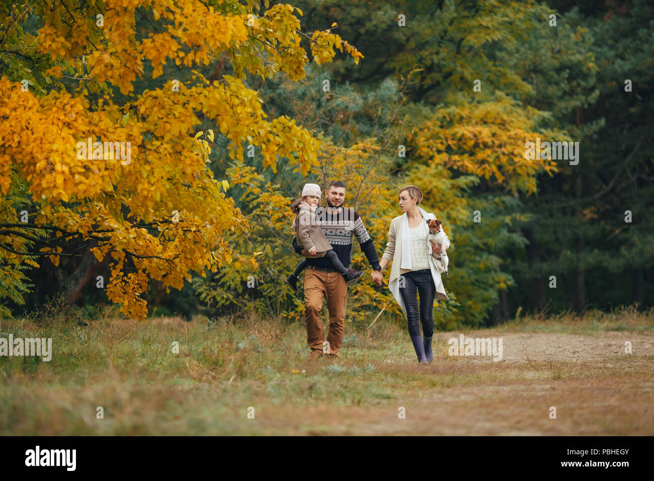 Young parents with their daughter hold hands and go at forest path with dog during walk in autumn forest. - Stock Image