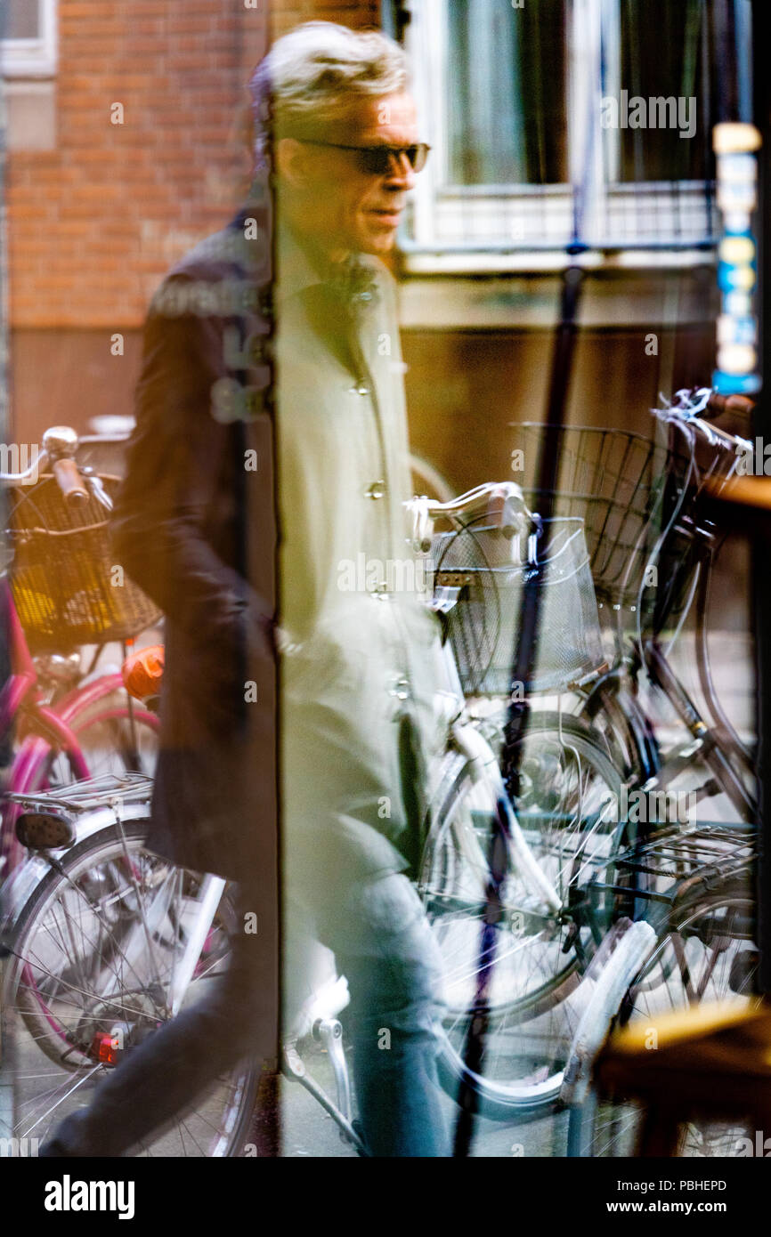 Man in coat and jeans with glasses passing by, seen through glass door, reflections, bicycles in background, photo taken from Vinhanen, Nørrebro - Stock Image