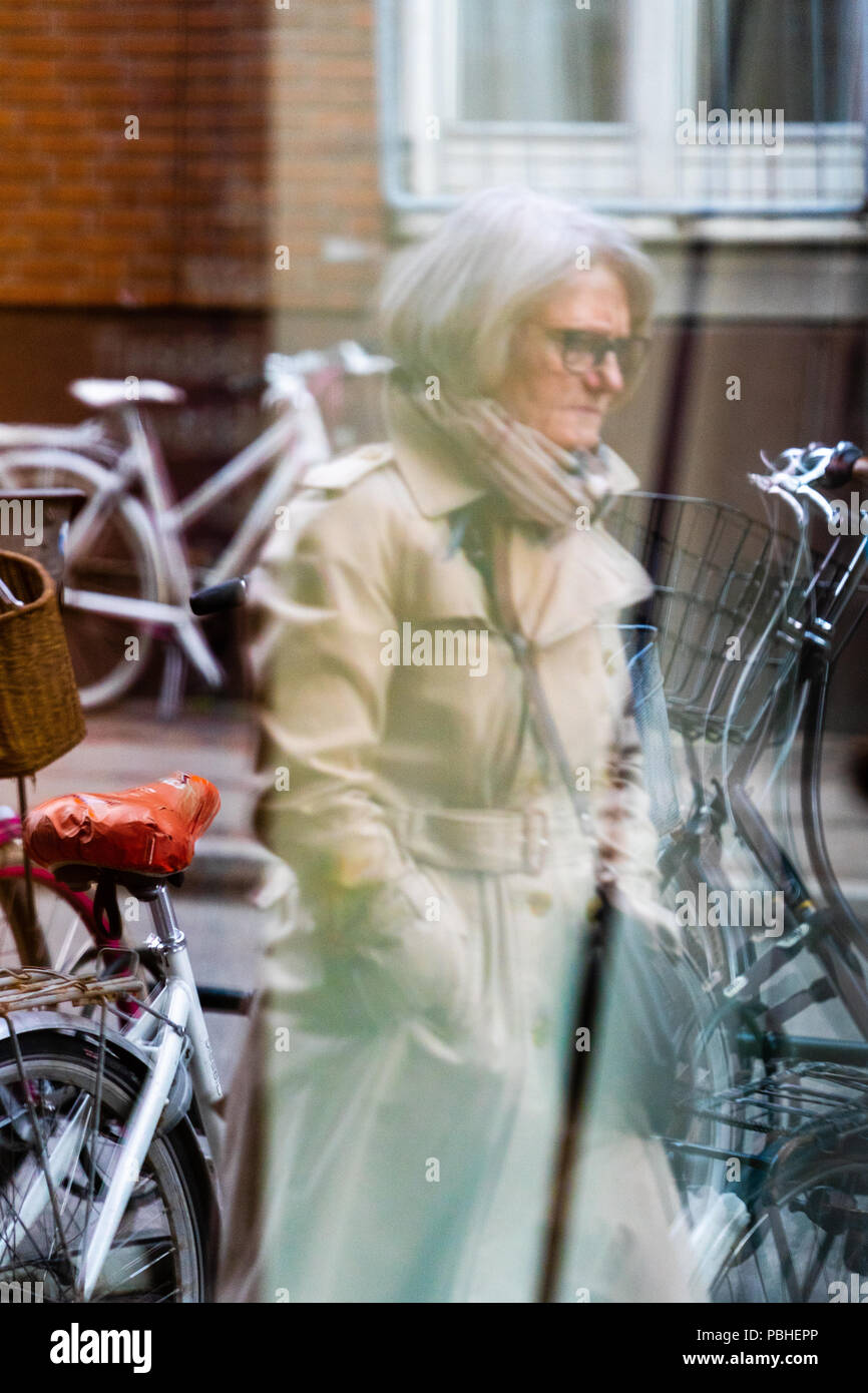 Woman in cotton coat wearing glasses, passing by, seen through glass door, reflections, bicycles in background, photo taken from Vinhanen, Nørrebro - Stock Image
