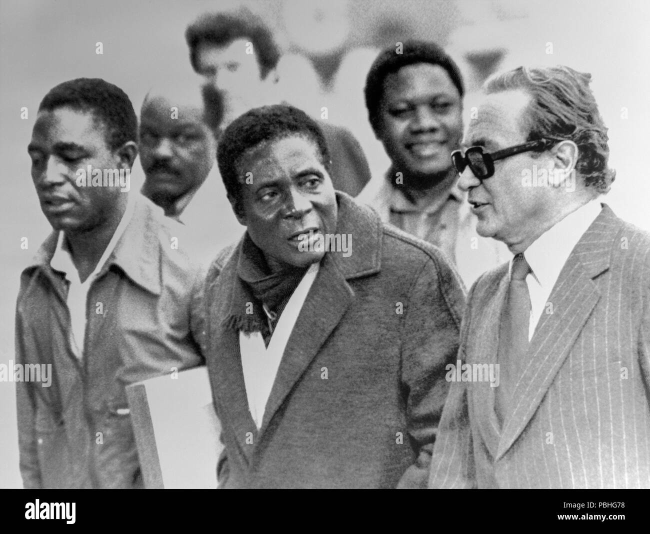 24th October 1976. Geneva, Switzerland. Guerrilla leader Robert Mugabe, Secretary General of the Zimbabwe African Nations Union, is accompanied by a Geneva Protocol Official as he and his party arrive in Geneva to attend the conference on Rhodesia. His group was the first black group to arrive for the talks. - Stock Image