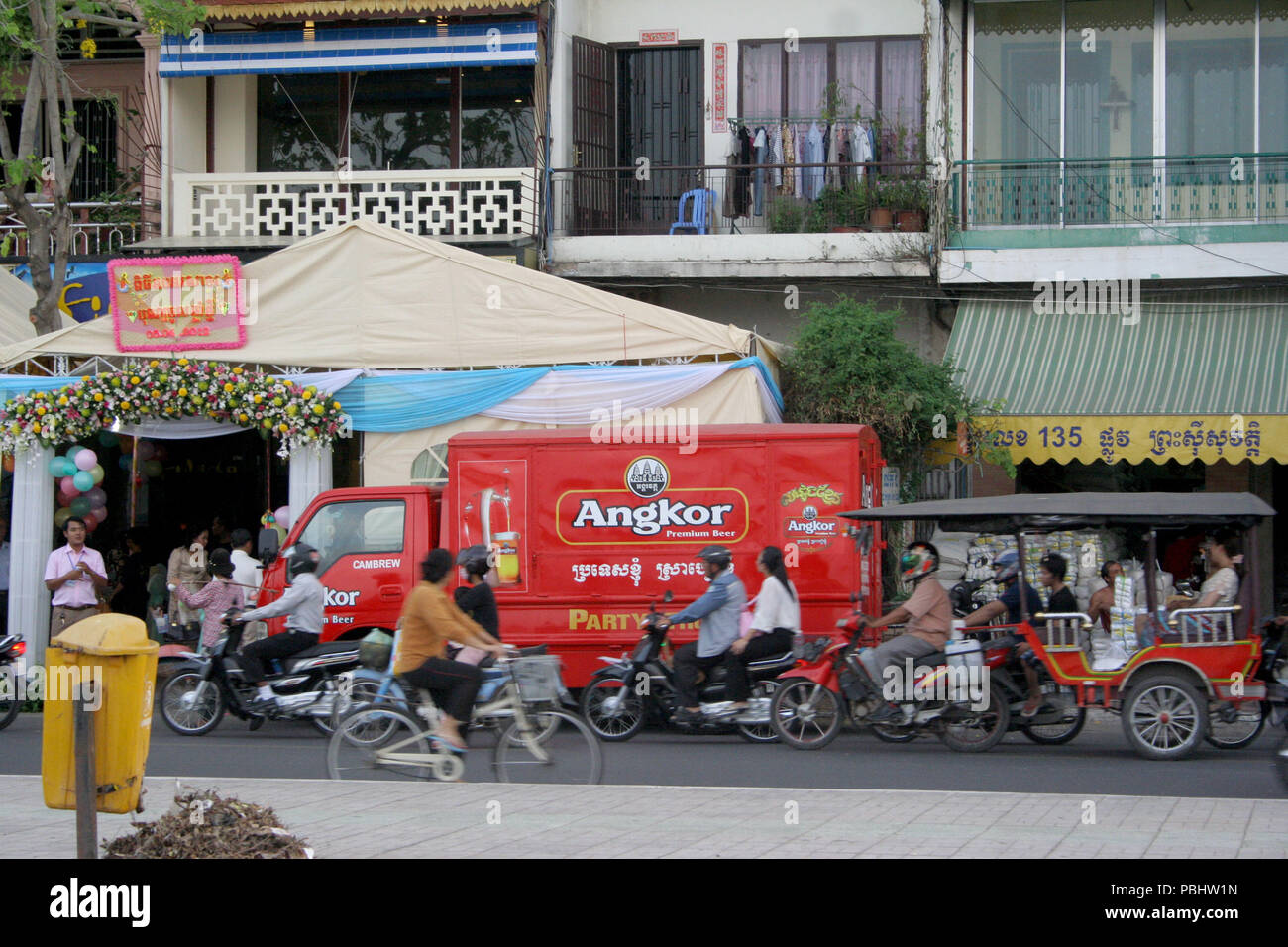 Red Van with Angkor Beer Graphics on Side in Busy Street, Phnom Penh, Cambodia - Stock Image