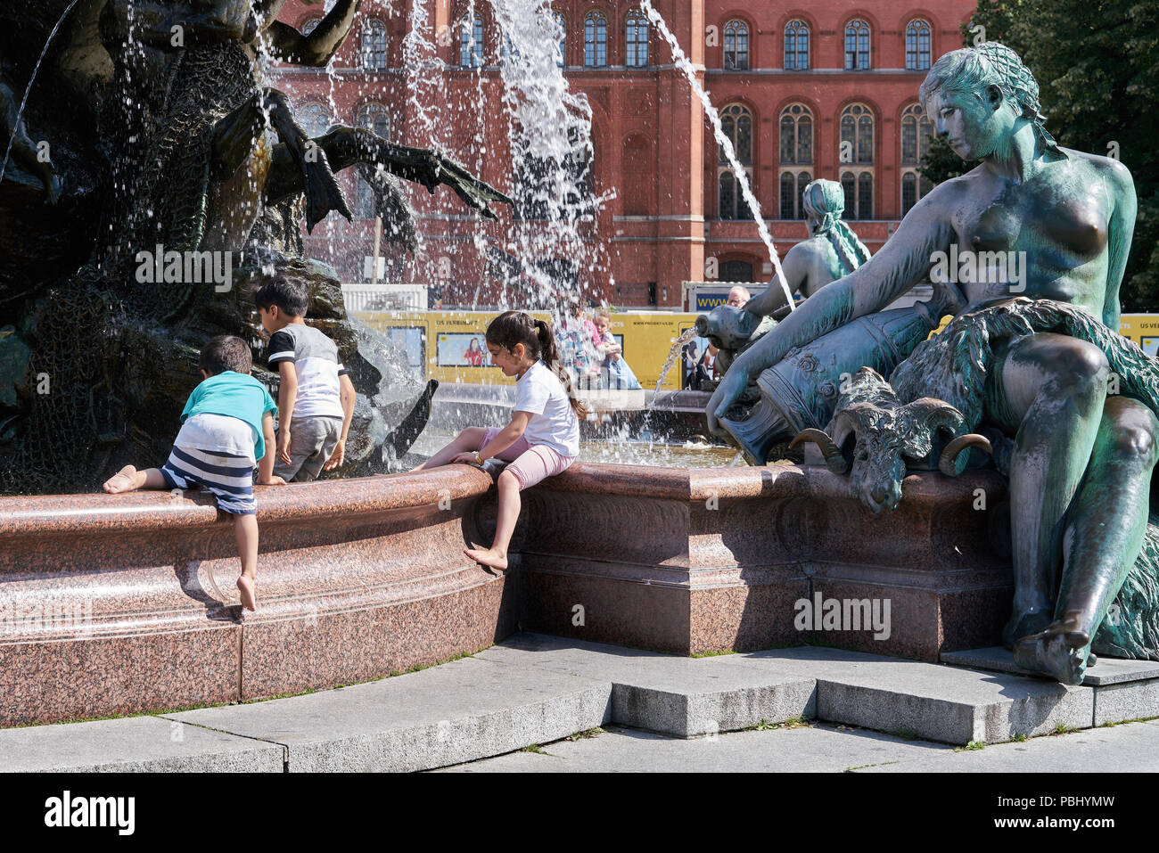 children playing at the Netun fountain in Berlin - Stock Image