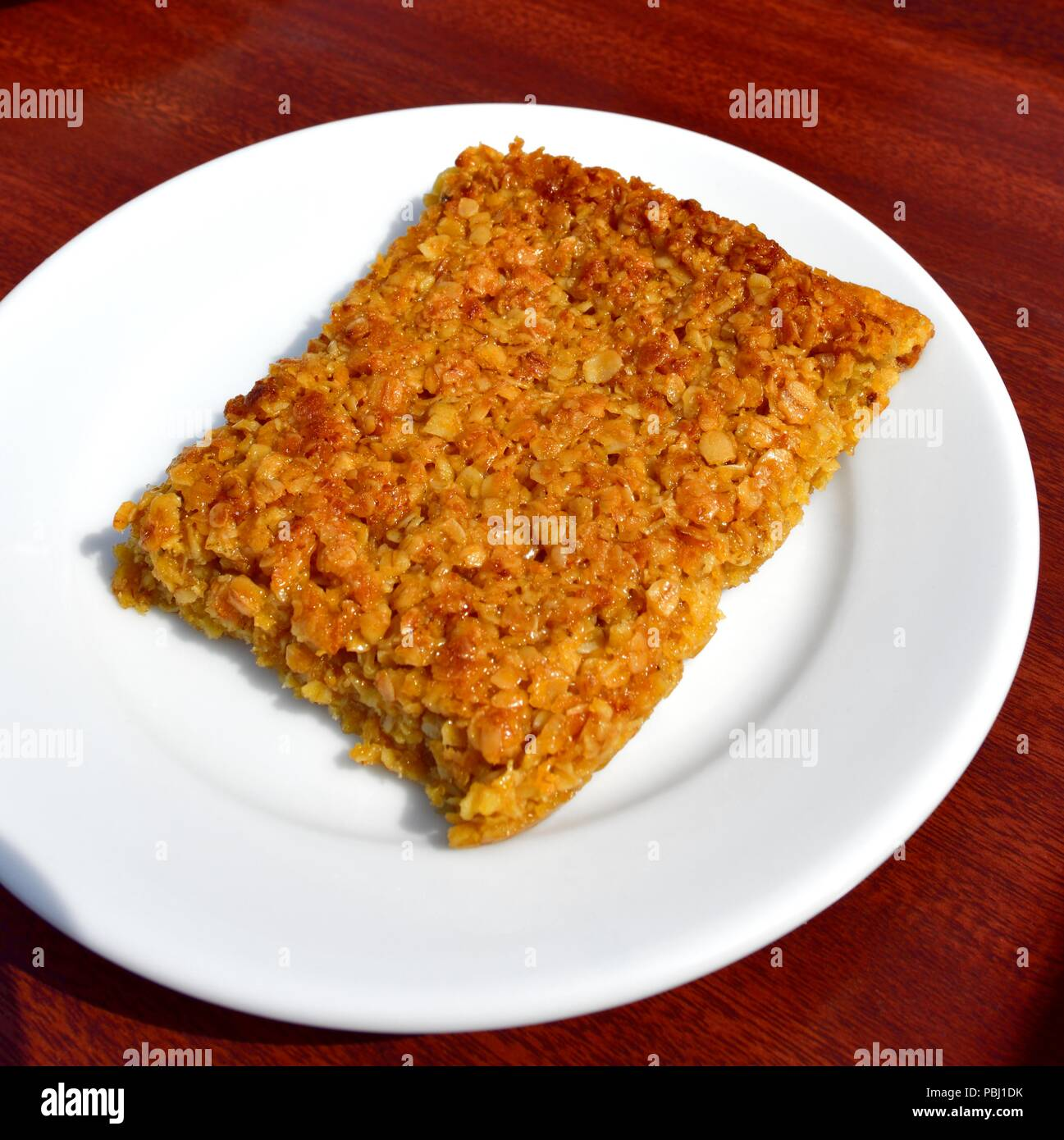 Flapjack on a white plate - Stock Image