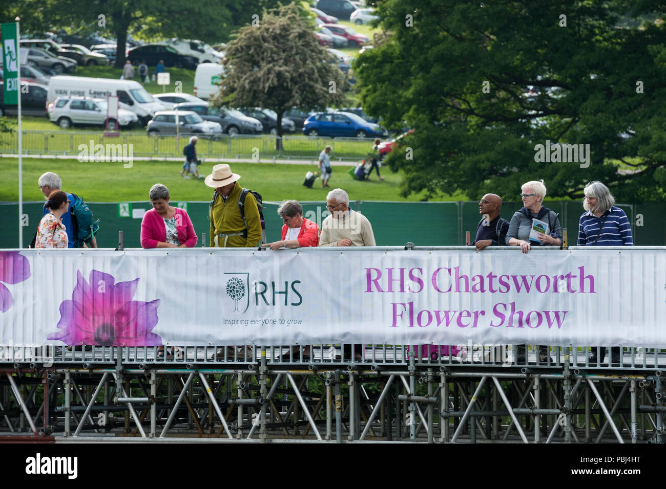 Showground visitors at RHS Chatsworth Flower Show, standing by promotional banner & looking over, temporary river bridge - Derbyshire, England, UK. - Stock Image