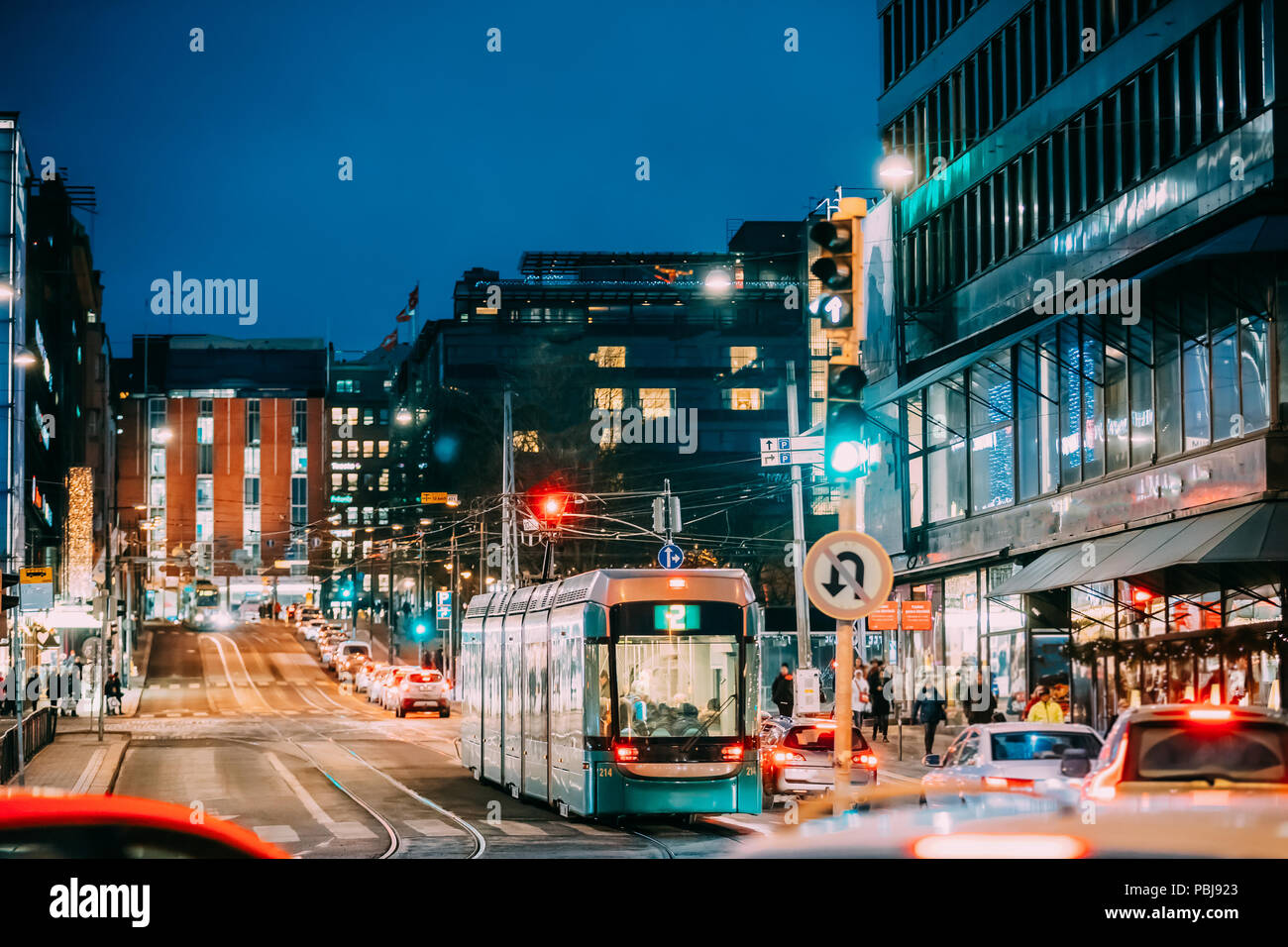 Helsinki, Finland. Tram Departs From A Stop On Kaivokatu Street In Helsinki. Night View Of Kaivokatu Street In Kluuvi District In Evening Or Night Ill - Stock Image