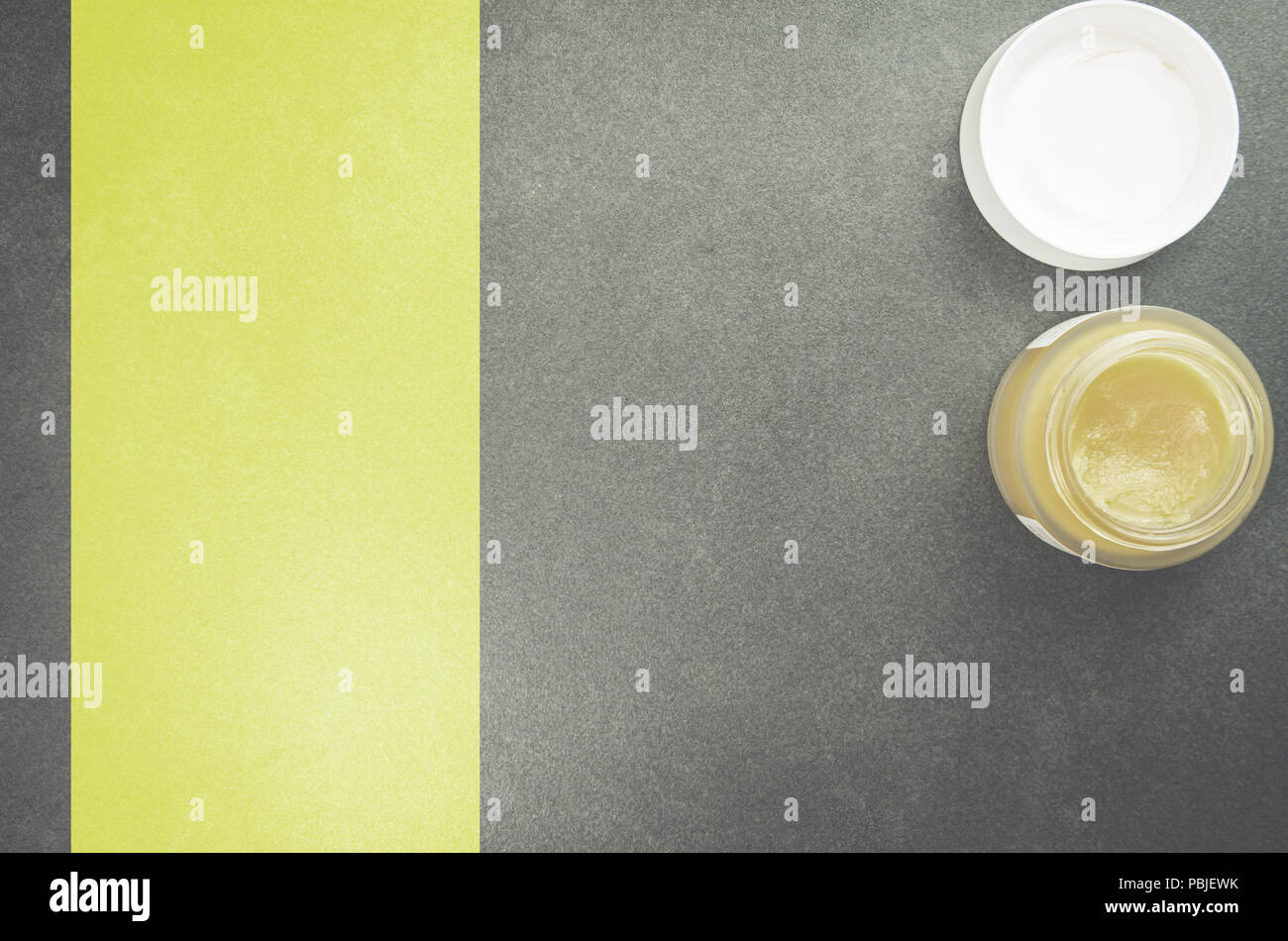 skin care cream container on a stone surface - directly above view - Stock Image