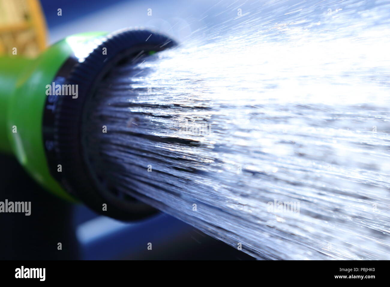 A shower of water from a hosepipe before the proposed hosepipe ban comes into effect. - Stock Image