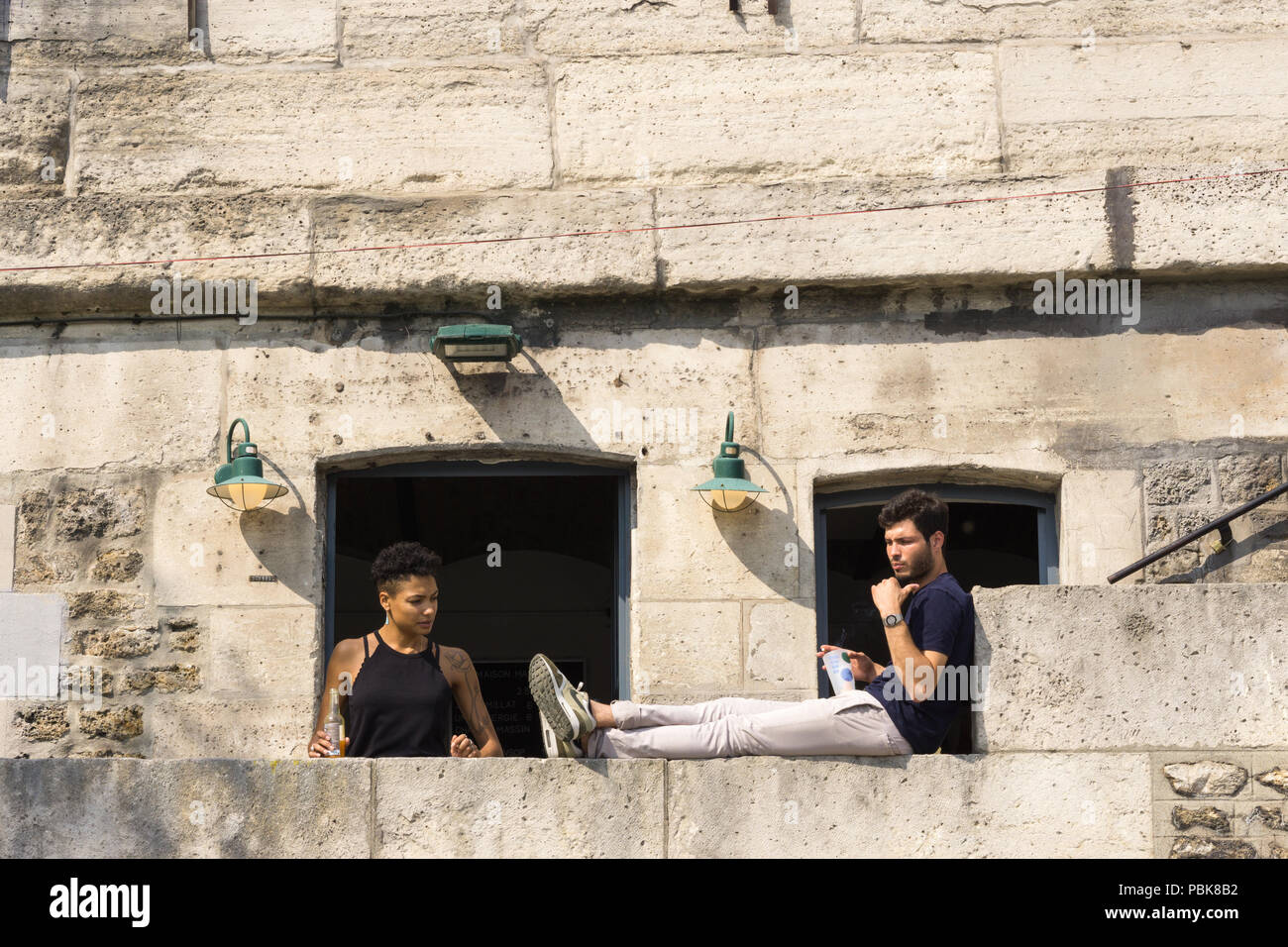 Paris people - Woman and man enjoying drinks in the Parc Rives de Seine during summer in Paris, France, Europe. - Stock Image