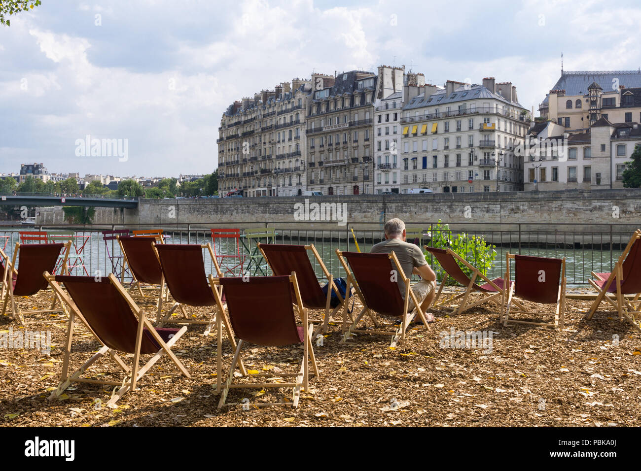 Man relaxing on the Seine River right bank during the Paris Plages event. - Stock Image