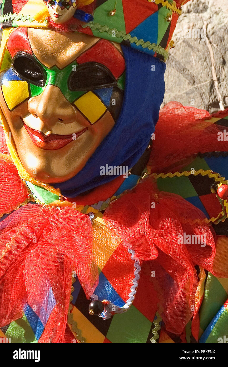 Masked reveller, Piazzetta San Marco, Venice: masker poses by the Porta della Carta - Stock Image