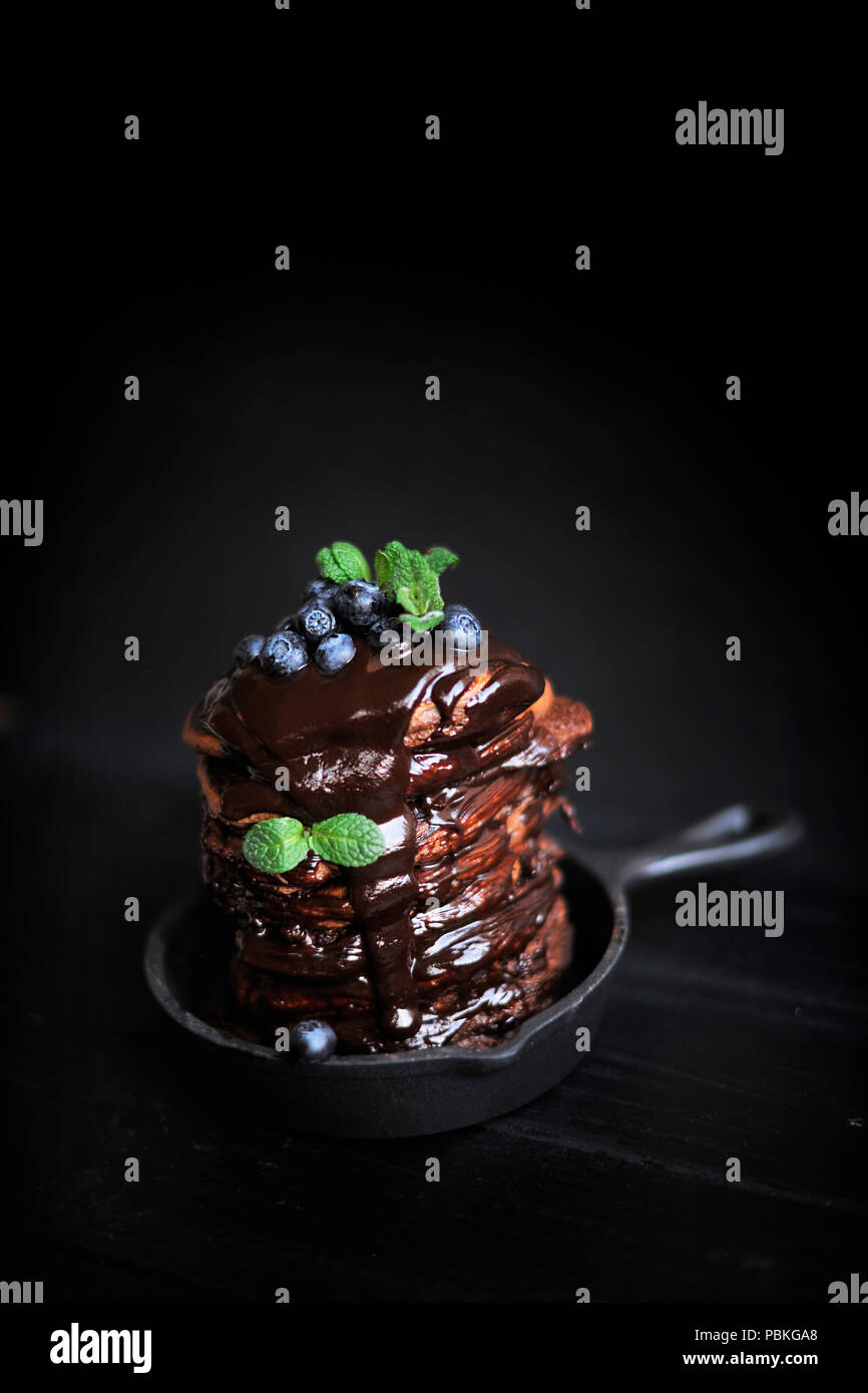 chocolate pancakes for breakfast with blueberries, dark photo. Homemade baking. - Stock Image