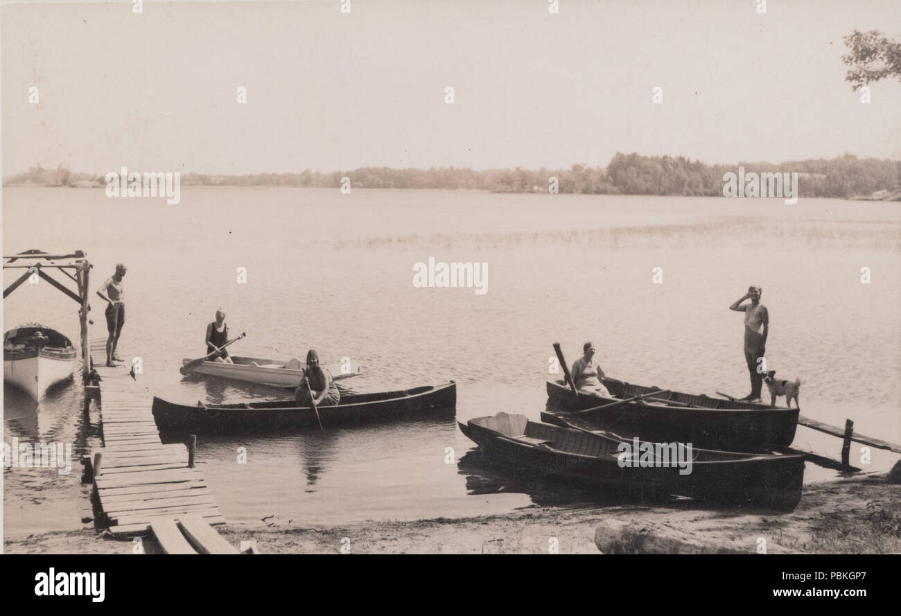 Vintage Photograph of People Using Boats and Canoes - Stock Image